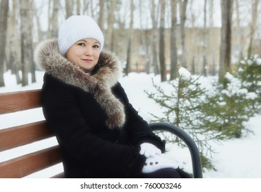 Young woman sits on the bench in a winter park outdoors