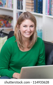 Young woman sits on the couch together with a laptop