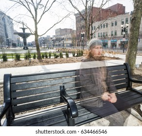 A young woman sits on a downtown city bench feeling invisible feeling the unseen difficulty of mental illness