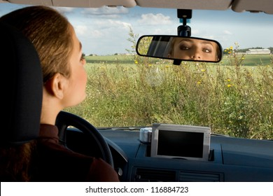 Young woman sits on driver's seat and Looks in the rear-view mirror.