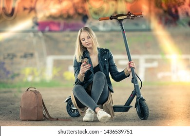 Young woman sits on e-scooter with smartphone and reads news