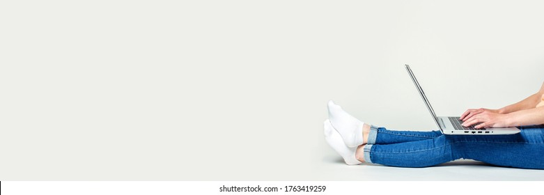 Young woman sits on the floor and works on a laptop on a light background. Banner. Freelance concept, work at home. No face visible