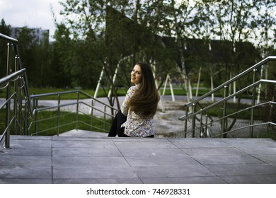 A young woman sits on the stairs and turns to the camera. Happiness. joy. Spring. heat.