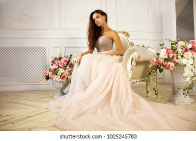 Young woman sits in a pink air dress in a armchair with flowers on a white wall background