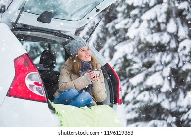 Young woman sits in the trunk of the car and holds a cup of hot drink in her hands.
