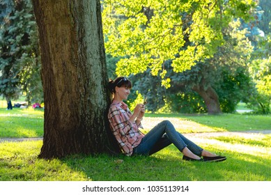 young woman sits under a tree with a phone in hands in the summer park