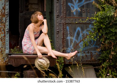 Young woman sitting in an abandoned train car.
