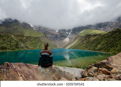 Young woman sitting alone contemplating the Humantay Lagoon at Perú.