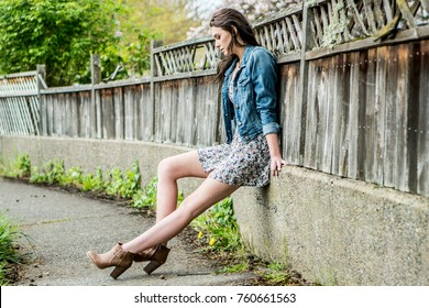A young woman sitting along a wooden fence in a urban  or suburban setting wearing a short bohemian style floral dress with a denim jacket.