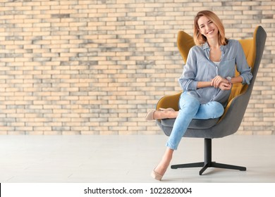 Young woman sitting in armchair indoors