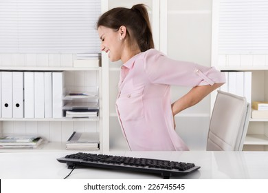 Young woman sitting with backache in the office.