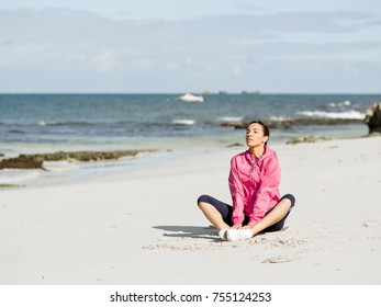 Young woman sitting at the beach in sportswear