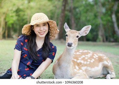 Young woman sitting with a beautiful wild deer