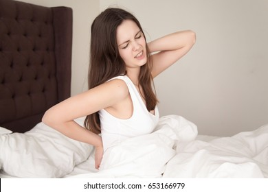 Young woman sitting in bed stretching and rubbing stiff back muscles after waking up in morning. Lady suffering from backache after sleep, feels discomfort because of bad mattress or posture problems