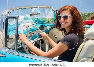 Young woman is sitting behind a steering wheel of a classic cuban car in Malecon in Havana, Cuba.