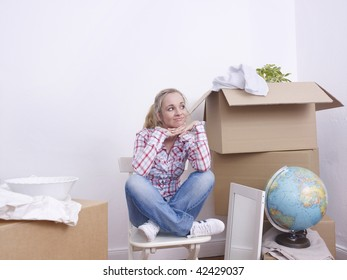Young woman sitting with brown boxes and household objects.