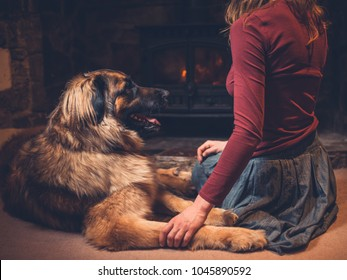 A young woman is sitting by the fire of a log burner with a giant dog