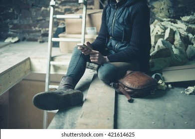 A young woman is sitting by herself in a derelict loft space and is using her cell phone