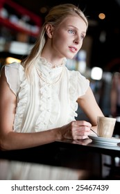 A young woman sitting in a cafe with a coffee