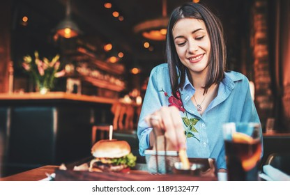 Young woman sitting in a cafe and enjoying in breakfast. Food, lifestyle concept
