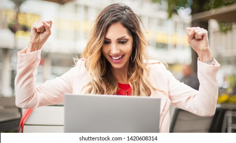 Young woman sitting in cafe, front of laptop raising her hands, she received an email with good news