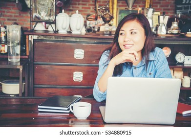 Young woman sitting in a cafe with her laptop, Stressful for work.