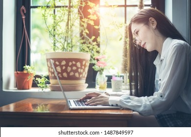 Young woman sitting at cafe table drinking coffee and working on laptop.