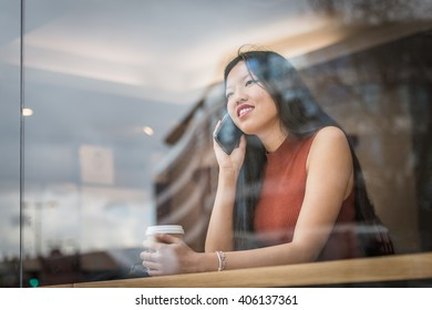 Young woman sitting at cafe' and talk to the phone