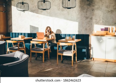 Young woman sitting at caffe, drinking coffee, working on laptop and talking at the phone.
