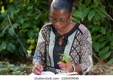 young woman sitting in camisole glasses in park with book and plant in hand going to write.