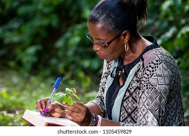 young woman sitting in camisole and glasses in park with plant in hand taking notes.