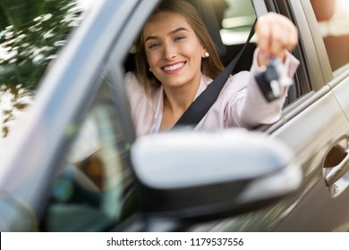 Young woman sitting in car holding car keys