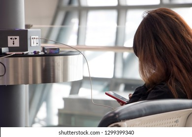 A young woman sitting at a charging station and looking at her smartphone. Recharging mobile phones from free charge station at the airport.