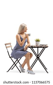 Young woman sitting at a coffee table isolated on white background
