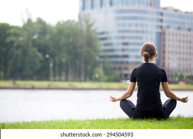 Young woman sitting cross legged on river bank in front of modern office building, meditating, practicing yoga Easy Pose, Sukhasana, asana for meditation, pranayama, breathing, back view, copy space