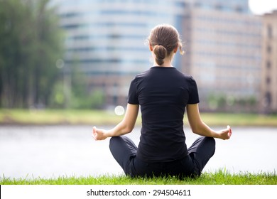 Young woman sitting cross legged on river bank in front of blue glass modern office building, meditating, practicing yoga Easy Pose, Sukhasana, asana for meditation, pranayama, breathing, back view