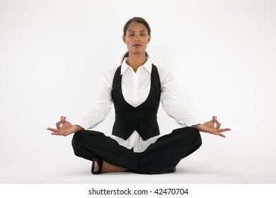Young woman sitting cross legged and meditating. Horizontally framed shot.
