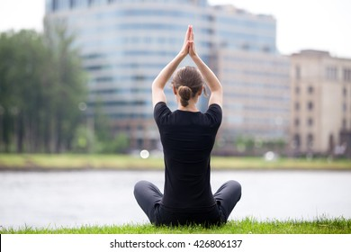 Young woman sitting cross legged on riverbank in front of blue glass modern office building, practicing yoga Easy Pose, Sukhasana, posture for meditation, pranayama, breathing, full length, back view