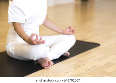 Young woman sitting cross legged on the floor doing yoga in studio
