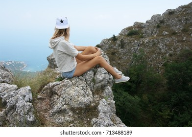 Young woman sitting with dangling legs on steep cliff and looking at distance.