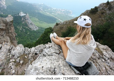 Young woman sitting with dangling legs on steep cliff and looking at distance. Back view.