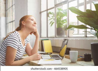 Young woman sitting daydreaming at the office leaning her chin on her hand and staring up out of a nearby window with a dreamy smile of pleasure
