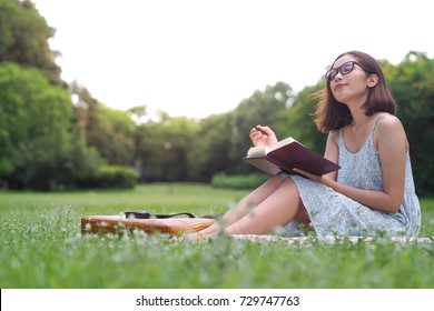 Young woman sitting daydreaming in the park