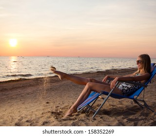 Young woman sitting in a deck chair on the beach by the ocean and watching the sunset