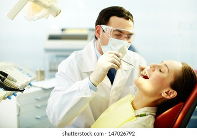 Young woman sitting in dentists chair while doctor examining her teeth