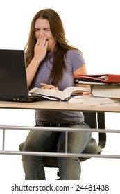 Young woman sitting at desk in front of laptop beside a pile of thick textbooks with hand over mouth yawning