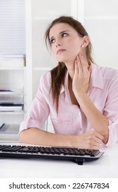 Young woman sitting at desk having pains in the neck or swollen lymph nodes,