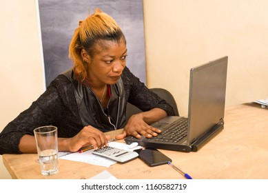 young woman sitting at desk looking at laptop.