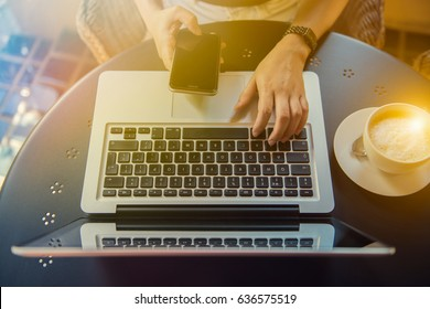 Young woman sitting at desk and typing on laptop and mobile phone ,hands close up. Female working on an outdoor cafe.