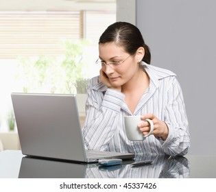 Young woman sitting at desk working with laptop computer at home, smiling.